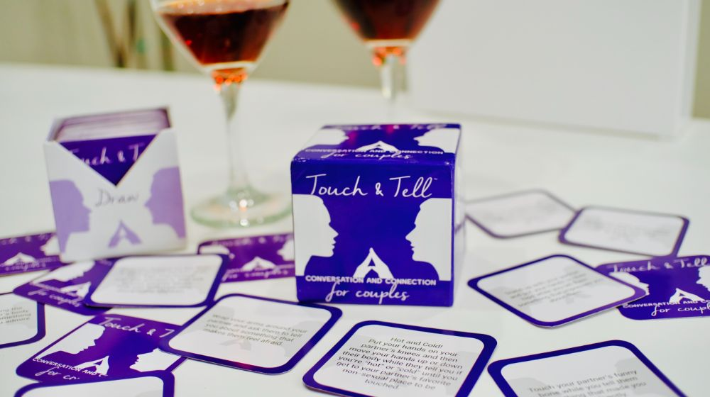 Touch & Tell Card Game with cards spread out, two glasses of wine in background